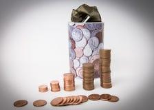 Ein Stapel Münzen, die eine Front des Metallgeldkastens lokalisiert stehen finanzierung Stockfotografie