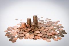 Ein Stapel Münzen am weißen Hintergrund, der durch andere Münzen umgeben wurde, wurde herum verschüttet Stockfoto