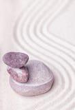 Ein Stapel purpurroter Quarz und beige Steine im feinen Sand Lizenzfreies Stockfoto
