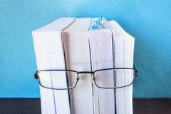 Ein Stapel starke neue Bücher und schwarze Gläser stellen ein Person ` s Gesicht dar Konzeptlesung, Vorbereitung für Prüfungen, T Lizenzfreie Stockfotografie