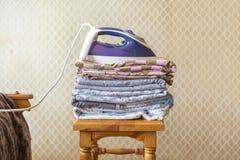 Ein Stapel Textilbettlakendecken mit Eisen auf Spitzenf stockfotografie