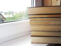 Ein Stapel von alten Büchern auf dem weißen Fensterbrett Lizenzfreies Stockfoto