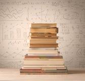 Ein Stapel von Büchern mit den Matheformeln geschrieben in Gekritzelart Stockbilder