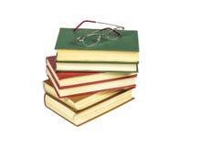 Ein Stapel von Büchern mit festem Einband und Lesebrille liegt auf einem hellen Ba Lizenzfreie Stockbilder