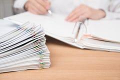 Ein Stapel von Dokumenten mit dem Mann lizenzfreie stockfotografie