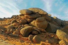 Ein Stapel von großen Flusssteinen in der ägyptischen Wüste gegen einen blauen Himmel stockfotos