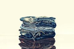 Ein Stapel von Jeans im Regal des Speichers oder auf dem Tisch reflexion Das Konzept: der Verkauf im Speicher Lizenzfreie Stockbilder