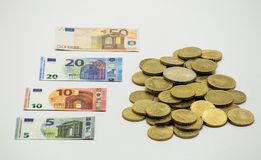 Ein Stapel von Münzen, der europäische Währung EURO mit Miniaturbanknoten 5, 10, 20, EURO 50 Lokalisiert auf weißem Hintergrund m Stockbild