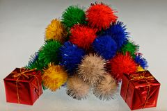 Ein Stapel von multi farbigen pom poms mit einem eingewickelten Geschenk in der Front stockfoto