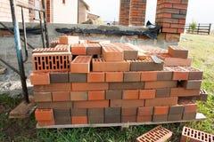 Ein Stapel von roten Backsteinen Bauen eines Hauses der Ziegelsteine Stockbild
