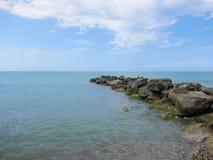 Ein Stapel von Steinen dehnt heraus in das Meer aus Stockfotografie