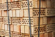 Ein Stapel Ziegelsteine des roten Lehms mit Löchern Lizenzfreie Stockfotos