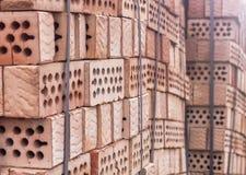 Ein Stapel Ziegelsteine des roten Lehms mit Löchern Lizenzfreies Stockfoto