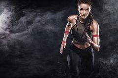 Ein starker athletischer, Frauensprinter, laufend auf dem schwarzen Hintergrund, der in der Sportkleidungs-, Eignungs- und Sportm