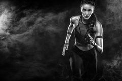 Ein starker athletischer, Frauensprinter, laufend auf dem schwarzen Hintergrund, der in der Sportkleidungs-, Eignungs- und Sportm lizenzfreie stockfotos