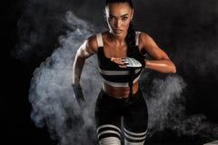 Ein starker athletischer, weiblicher Sprinter, laufend bei dem Sonnenaufgang, der im Sportkleidungs-, Eignungs- und Sportmotivati stockbild