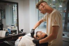 Ein starker gutaussehender Mann, der durch einen Berufsfriseur in einem Friseursalon auf einem Licht rasiert erhält, verwischte H stockbild