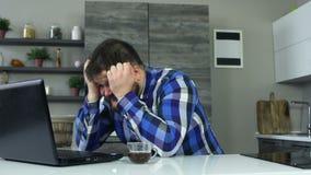 Ein starker Kerl ist in der Küche vor einem Laptop verärgert an und fängt, zu werden, schlägt die Tabelle mit seiner Hand Ein fet stock video footage