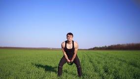 Ein starker Mann demonstriert eine Übung mit Gewicht Anheben des Pendels mit beiden Händen Klarer blauer Himmel, grünes Feld fron stock footage