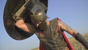 Ein starker römischer Krieger in der Rüstung mit einer Tätowierung auf seinem Arm wird mit einem Schild, Zeitlupe bedeckt