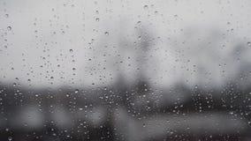 Ein starker Regen im Sommer in Deutschland - durch gesehen der Fensterscheibe mit dem Fokus auf Regentropfen stock footage