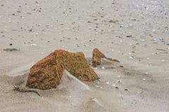 Ein Stein auf einem Strandsand Stockfotografie