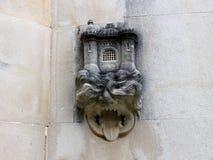 Ein Stein schnitzte Kopf mit einer Zunge heraus auf der Wand einer neo-gotischen Kapelle in Quinta da Regaleira in Sintra Lizenzfreie Stockfotografie