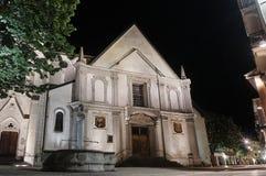 Ein Steinbrunnen und eine Fassade einer mittelalterlichen Kirche stockbilder