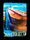 Ein Stempel, der in Australien gedruckt wird, zeigt ein Bild ` schweres Schlepper ` des roten Frachtschiffs auf einem Wert an Lizenzfreies Stockbild