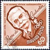 Ein Stempel, der in Ungarn gedruckt wird, zeigt ein Porträtbild von Pierre de Coubertin Lizenzfreie Stockbilder