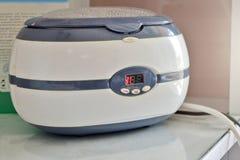 Ein Sterilisator oder eine Desinfektionsmaschine in einer flüssigen Lösung in einem Schönheitssalon in Arbeitsprozeß stockfotografie
