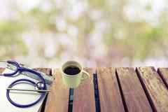 Ein Stethoskop, Krankengeschichteordnerklemmbrett-, Bleistift- und Kaffeetassestapel auf Plattform Stockfoto