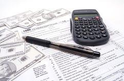 Ein Steuerformular-Bargeld und ein Taschenrechner Stockbild