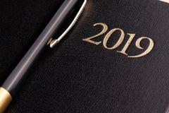 Ein Stift auf einem geschlossenen schwarzen Notizbuchtagebuch mit der Aufschrift 2019 stockfotos