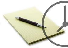 Ein Stift auf einem Notizbuch mit einer Uhr für Geschäftsabschluß oben Lizenzfreies Stockfoto
