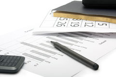 Ein Stift, ein Handy, ein Notizbuch und Finanzberichte Stockfotografie