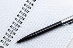 Ein Stift steht auf einem Notizblock still Lizenzfreie Stockbilder