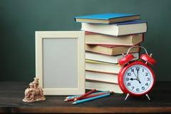 Ein Stillleben mit Büchern, einem Wecker und einem Rahmen für ein Foto Stockbilder