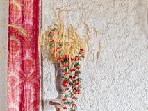 Ein Stillleben mit einem Vase Getreide und Weizen und roten Blumenranken lizenzfreie stockfotos