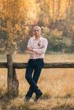Ein stilvoller, erwachsener, erfolgreicher Mann steht auf dem Hintergrund eines Bretterzauns Der Kerl wird in einem rosa Hemd und stockbilder