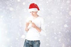 Ein stilvoller Kerl in einem Sankt-Hut feiert Weihnachten und ein neues Jahr Lizenzfreies Stockfoto