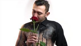 Ein stilvoller Mann in der Kunst des schwarzen Körpers riecht eine rote Rose stock footage