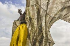 Ein stolzes stitwalker oder ein Moko Jumbie, während sie in Trinidad und Tobago genannt werden, verlängert sein Kap am Karnevals- lizenzfreies stockbild