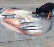 Ein Straßenkünstler bei der Arbeit kniend aus den Grund in London-` s Trafalgar-Platz stockfotografie