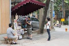 Ein Straßenkünstler ist Service für einen Jungen Lizenzfreies Stockbild