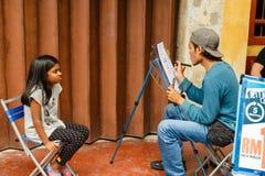 Ein Straßenkünstler malt ein Porträt eines Mädchens Lizenzfreies Stockfoto