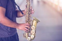 Ein Straßenmusiker spielt das Saxophon mit undeutlichen Leuten stockfoto