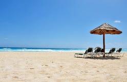 Ein Strandstuhl und -regenschirm auf einem tropischen Strand. Lizenzfreies Stockfoto