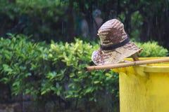 Ein Strohhut, ein einfacher thailändischer Besen und eine gelbe Mülltonne; alle schnell verlassen wegen eines plötzlichen Sommerr stockfotografie