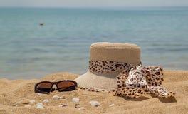 Ein Strohhut für eine Leoparddruckfrau, -Sonnenbrille und -Muscheln durch das Meer stockfotos